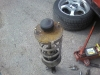 Išimtas automobilio galinis amortizatorius - korozijos pažeista atraminė plokštelė